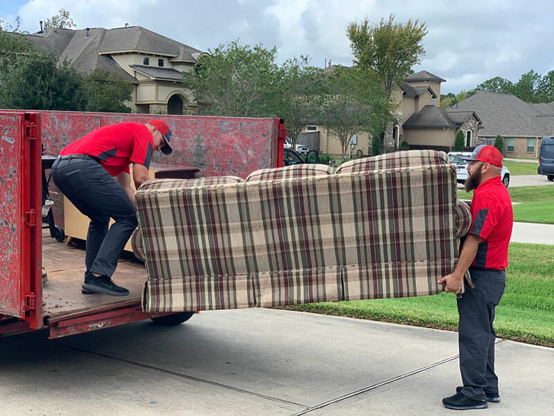 4 Alarm Junk Removal employees putting a couch in the truck